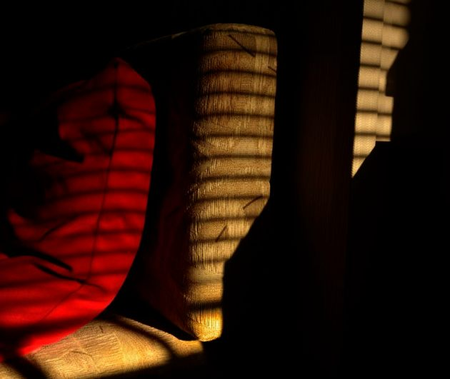 The sun, shining through blinds onto cushions