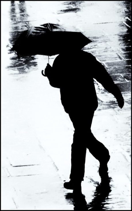 Man walking in the rain, with an umbrella, in Bristol