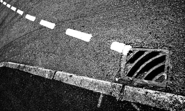 drain-with-kerb-dashed-white-line-and-skid-marks-mono