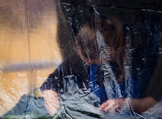 woman-working-behind-a-transparent-plastic-sheet